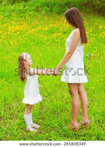 Mother and daughter walking and having fun together in summer day, mom with child outdoors - stock photo