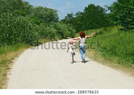 Mother and daughter walking by rural road among trees in lovely summer day - stock photo
