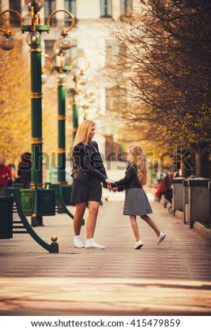Mother and daughter walking holding hands at park. They are wearing dresses and jackets. Family lifestyle concept - stock photo