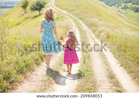 mother and daughter walking holding their hands - stock photo