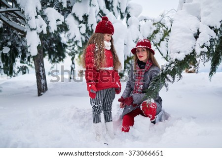 Mother and daughter walking in a snowy park