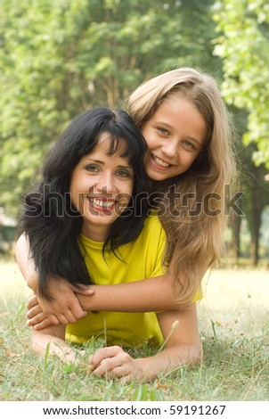 Mother and daughter walking in a summer park