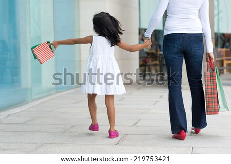 Mother and daughter walking in the city with paper bags, rear view - stock photo