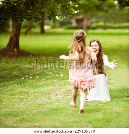 mother and daughter walking in the park, happy at sunset in Bangkok, Thailand. - stock photo