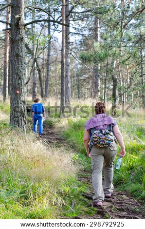 Mother and daughter walking in the woods on sunny spring day. - stock photo
