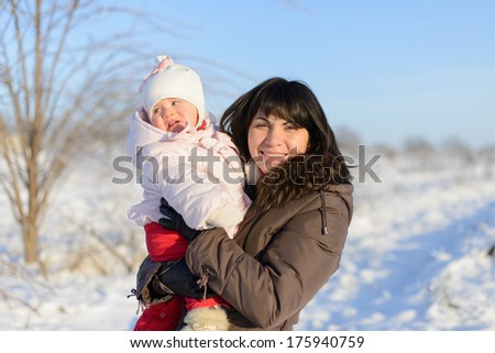 mother and daughter walking in winter day - stock photo