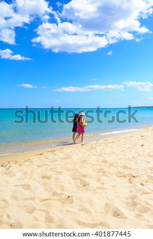 Mother and daughter walking on the beach, tropical sea on background - stock photo