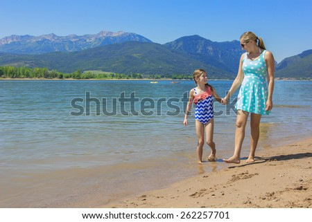 Mother and daughter walking together at scenic lake  - stock photo