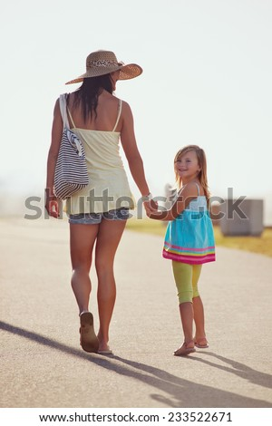 Mother and Daughter walking together at the beach holding hands in summer - stock photo