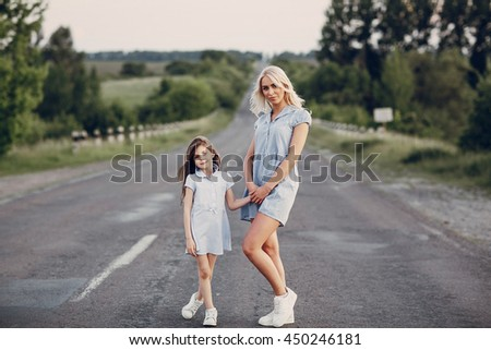 mother and daughter walking together in a field in Sunny summer weather - stock photo