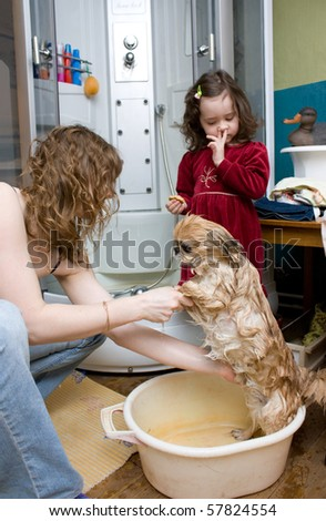 Mother and daughter washing a red dog in a bathtub
