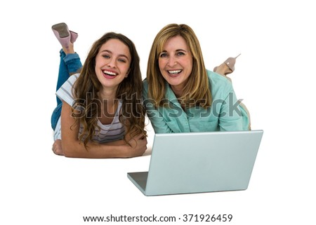Mother and daughter watch computer lying on the ground - stock photo