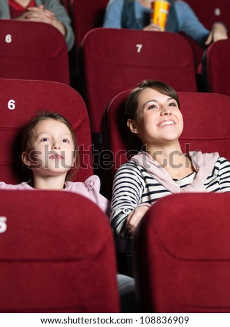 Mother and daughter watching movie - stock photo