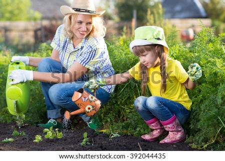 Mother and daughter watering plants in garden.