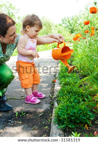 Mother and daughter watering plants in the garden - stock photo