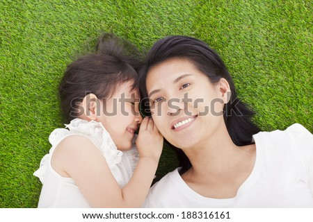 mother and daughter whispering gossip on the grass - stock photo
