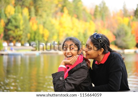 Mother and daughter whispering in outdoors - stock photo