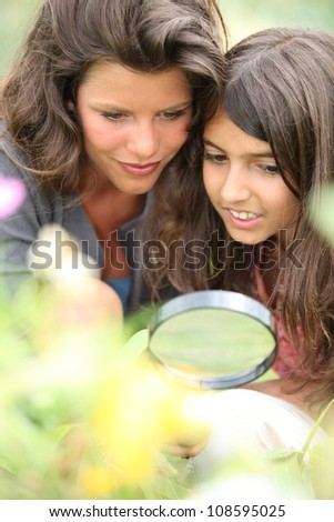 Mother and daughter with a magnifying glass - stock photo