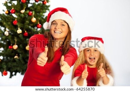 mother and daughter with christmas hats showing thumbs up - stock photo