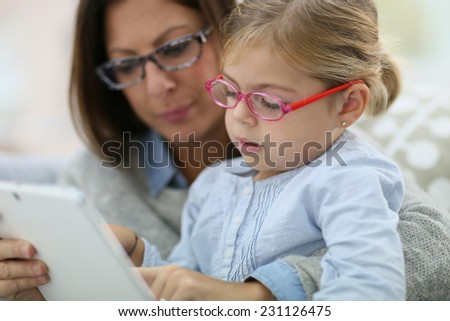 Mother and daughter with eyeglasses playing with tablet - stock photo