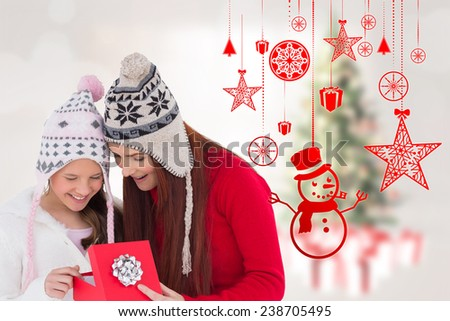 Mother and daughter with gift against blurry christmas tree in room - stock photo