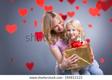 Mother and daughter with gift in studio - stock photo