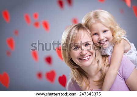 Mother and daughter with hearts - stock photo