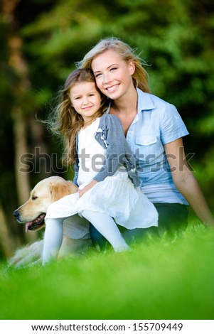 Mother and daughter with labrador sitting on the grass at the summer park
