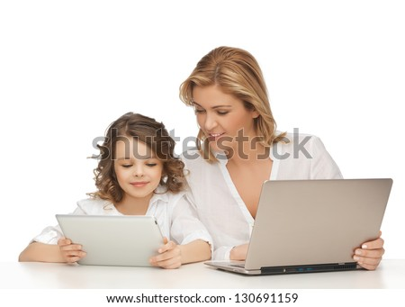 mother and daughter with laptop and tablet pc - stock photo