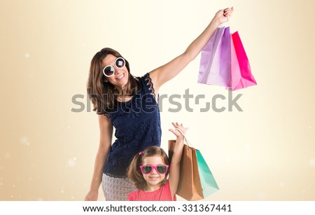 Mother and daughter with many shopping bags - stock photo