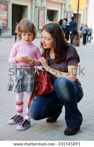 Mother and daughter with mobile phone in the street - stock photo