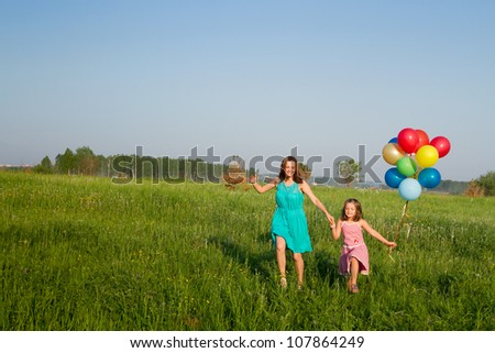 Mother and daughter with multicolored balloons - stock photo