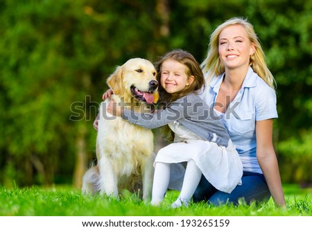 Mother and daughter with pet sitting on the grass at the summer park - stock photo
