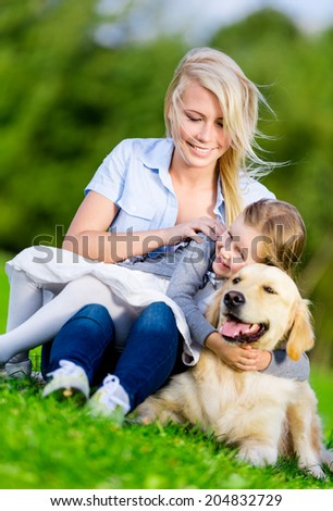 Mother and daughter with retriever sitting on the green grass at the summer park