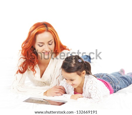 Mother and daughter with the tablet pc isolated on white background - stock photo