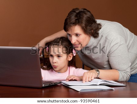 Mother and Daughter work on homework together at the kitchen table