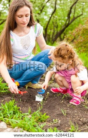 Mother and daughter working in garden - stock photo