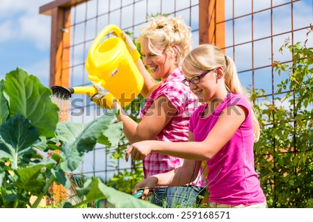 Mother and daughter working in garden watering plants with can  - stock photo