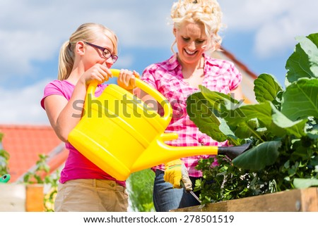 Mother and daughter working in garden watering plants with can in front of their house - stock photo