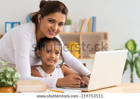 Mother and daughter working on laptop - stock photo