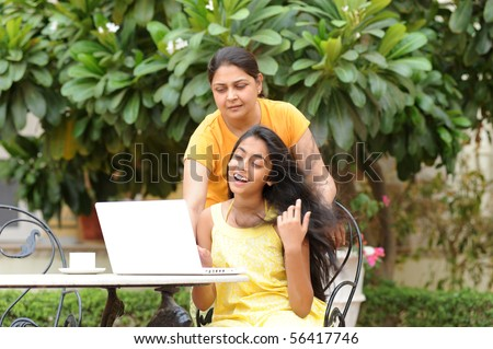 Mother and daughter working on laptop in outdoors - stock photo