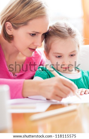Mother and daughter writing together - stock photo