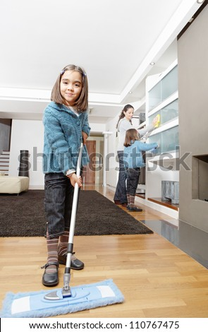 Mother and daughters cleaning the house together, smiling. - stock photo