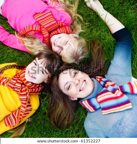 Mother and daughters lying on grass - stock photo