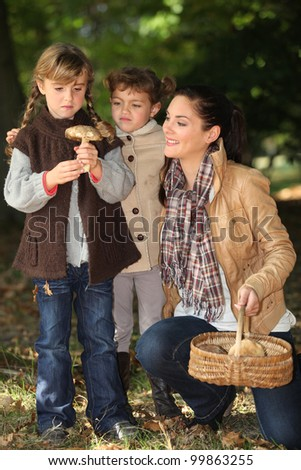 Mother and daughters picking mushrooms - stock photo