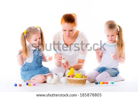 Mother and daughters playing with Easter eggs - stock photo