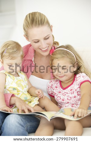 Mother And Daughters Reading Book At Home - stock photo