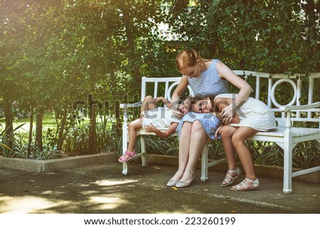 Mother and daughters relax outdoors - stock photo