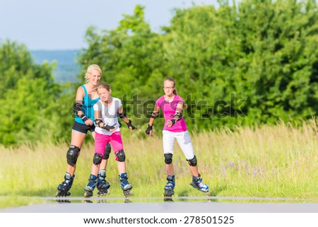 Mother and daughters rollerblading with in-line skates on country lane - stock photo