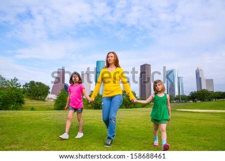 Mother and daughters walking holding hands on modern city skyline over park green lawn - stock photo